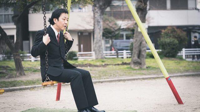 公園のブランコでボーっとしているサラリーマン