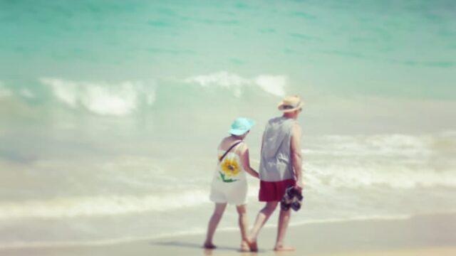 浜辺で散歩している老夫婦