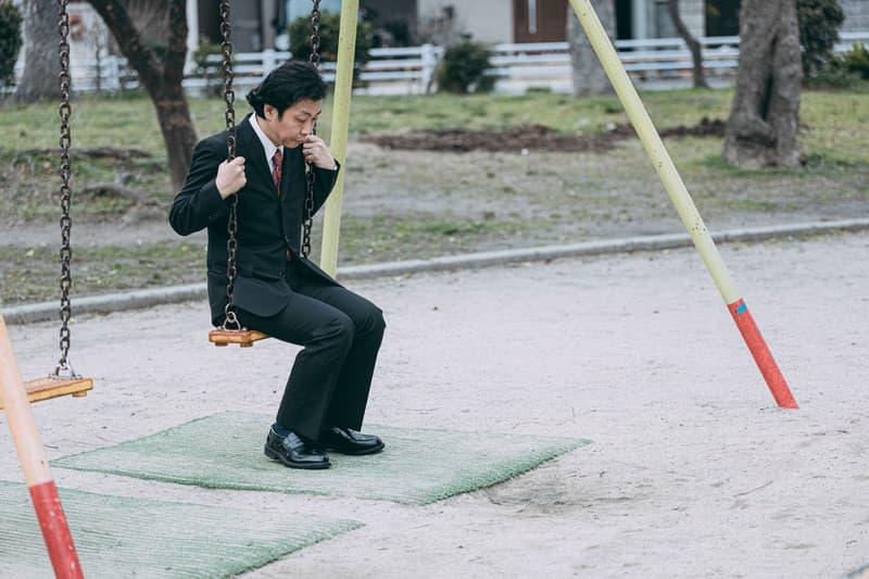 公園のブランコに乗る中年サラリーマン
